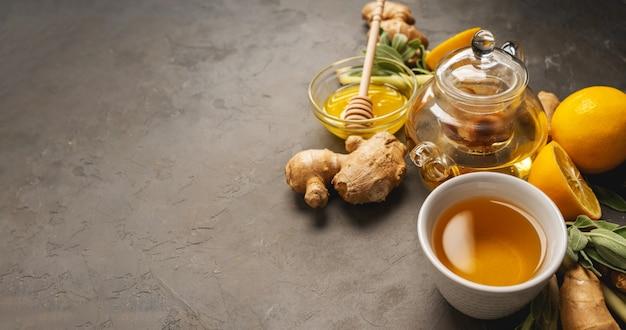 コピースペースと暗い背景に新鮮な生inger、レモングラス、セージ、蜂蜜、レモンで健康的な抗酸化剤と抗炎症ジンジャーティーを作る。
