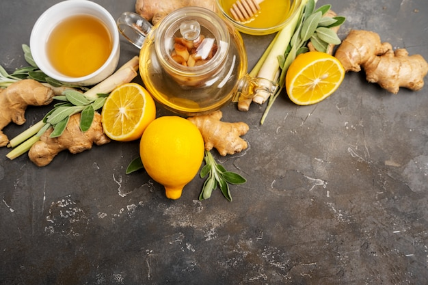 Making healthy antioxidant and anti-inflammatory ginger tea with fresh ginger, lemongrass, sage, honey and lemon on dark background with copy space.