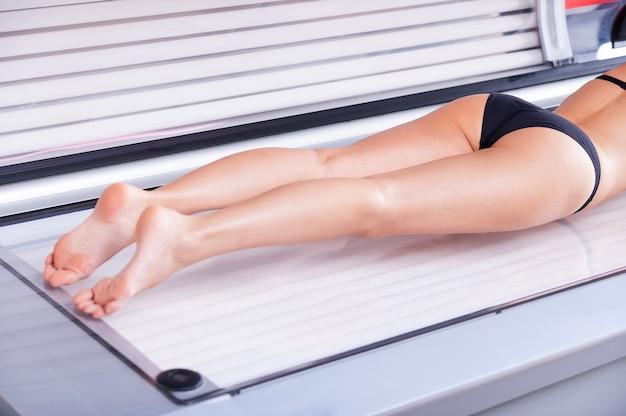 그녀의 아름다운 몸을 검게 만듭니다. 선탠 침대에 누워 있는 젊은 여성의 자른 이미지