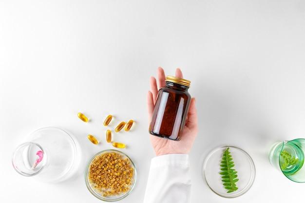 식물 잎 실험실에서 허브식이 보충제 만들기. 건강과 미용 개념