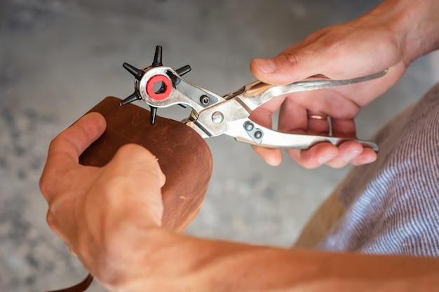 Изготовление дырок с перфоратором в кожаном цехе. мужские руки с перфоратором, работающим с куском материала