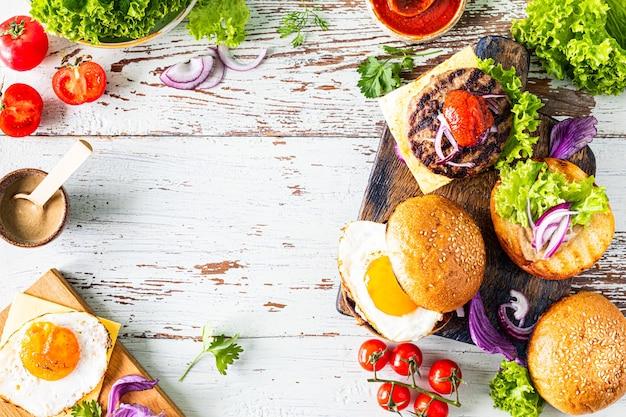Приготовление домашнего бургера. ингредиенты для приготовления на деревянном столе. вид сверху или плоская. копировать пространство