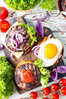 Приготовление домашнего бургера. ингредиенты для приготовления на деревянном столе. вид сверху. вертикальный