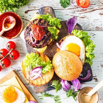 Приготовление домашнего бургера. ингредиенты для приготовления на деревянном столе. вид сверху.