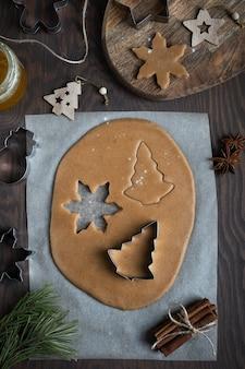 テーブルの上にシナモンと蜂蜜を入れたおいしい甘い生地から自家製ジンジャーブレッドクッキーを作る