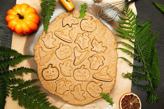 Making homemade gingerbread cookies. halloween symbols - pumpkin, hat, ghost. autumn food background.