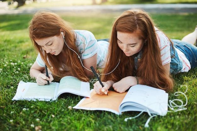 Делать домашнее задание может быть весело. снимок на открытом воздухе: две привлекательные рыжие девушки с веснушками лежат на траве в парке, деля наушники и пишут эссе для университета на свежем воздухе, помогая друг другу.