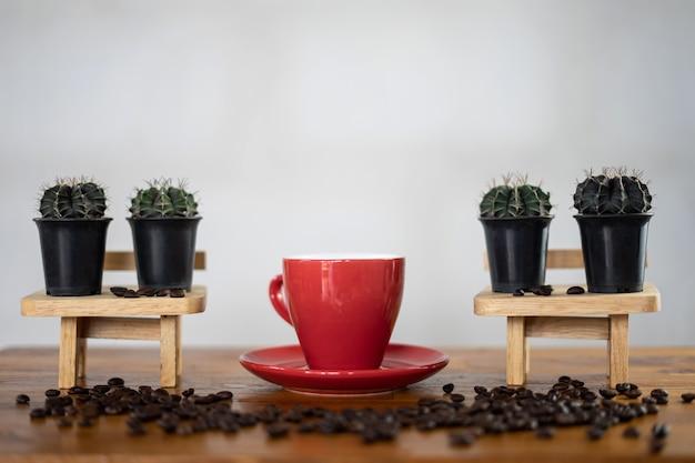 木製のテーブルでホットコーヒーを作る。エスプレッソコーヒーとサボテンの背景を持つコーヒー豆は、その日のリラックスしたコンセプトのテーブルに表示されます。