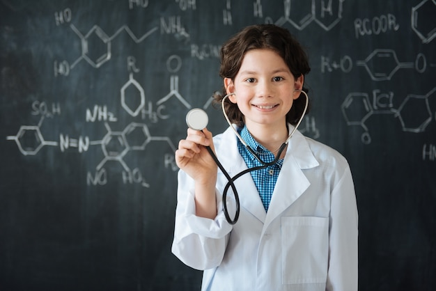 Making important choise. delightful smiling skilled teenager standing near the blackboard at school while enjoying medical class and using stethoscope