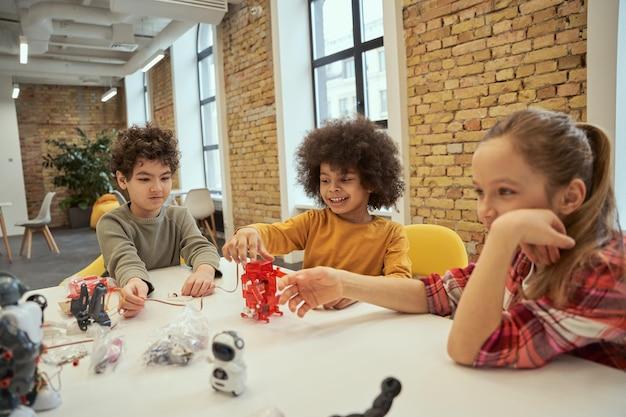 Делаем обучение увлекательным. разнообразные дети веселятся вместе, изучая технические детали.