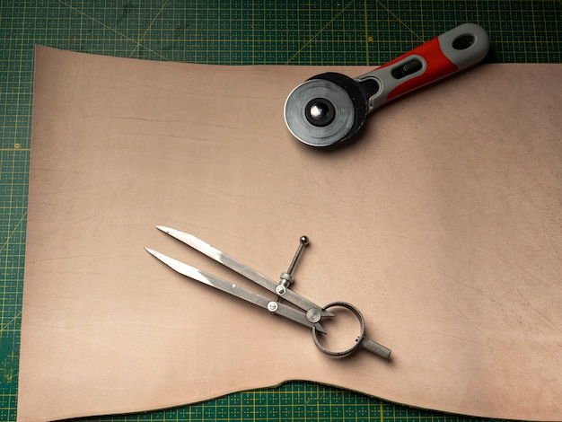Making a leather case for batteries by a tanner, on a green self-healing mat, leather craftsmanship concept