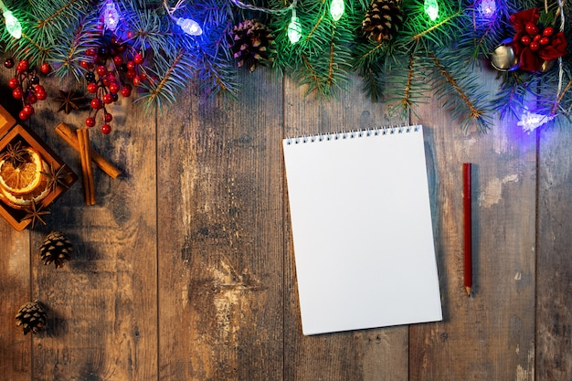 Making a to-do list or plan for next year. christmas tree branch and lights on wooden background.