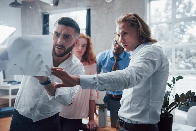 Делать отметки. молодая многорасовая команда в официальной одежде в офисе, глядя на прайс-лист