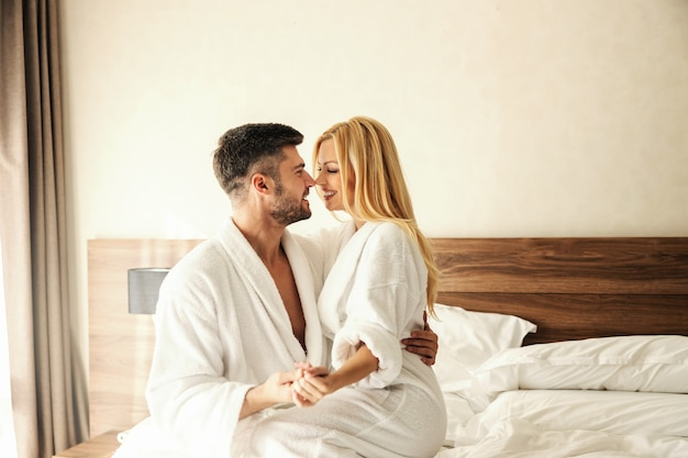 Сделать воспоминания в гостиничном номере нежными объятиями и поцелуями. красивая улыбающаяся пара, милая блондинка женщина и красивый мужчина в белых халатах наслаждаются постели с чистой кроватью любовная пара милые птицы