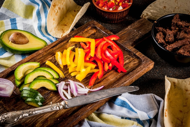 Making mexican pork tacos with vegetables and salsa