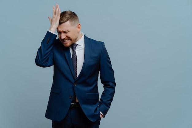 Совершая ошибку. подавленный деловой человек в костюме держит руку на лице и чувствует разочарование и стресс из-за плохих негативных новостей или бизнес-неудач