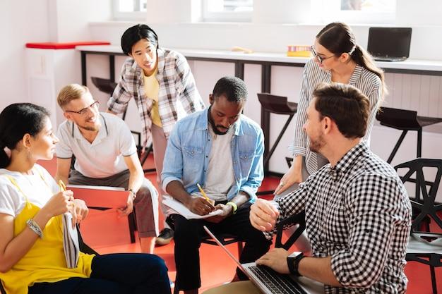 메모 만들기. 조용히 집중된 젊은 교사가 연필을 들고 자신의 영리한 학생 그룹의 최고의 아이디어를 들으면서 내려 놓습니다.