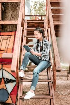 Делать заметки. веселая брюнетка женщина сидит на лестнице, глядя на свой гаджет