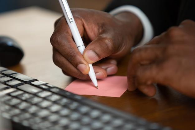 메모를 작성하고 닫습니다. 아프리카 계 미국인 기업가, 사업가 작업 사무실에 집중. 고전적인 정장을 입고 세리오스와 바쁘게 보입니다. 일, 금융, 비즈니스, 성공, 리더십의 개념.