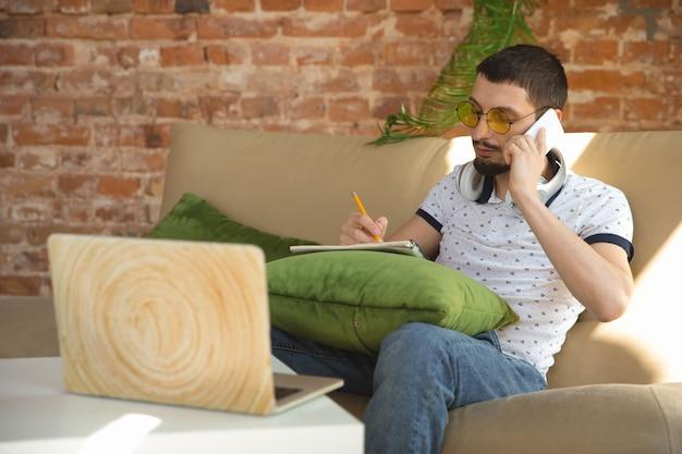 メモをとる。コロナウイルスまたはcovid-19検疫、リモートオフィスの概念の間に在宅勤務の男性。スマートフォン、コンピューターでタスクを行うマネージャーである青年実業家は、オンライン会議、会議を行っています。