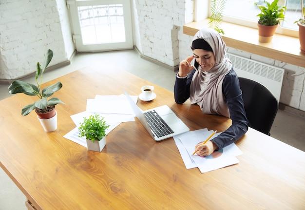 전화 통화 중 메모 작성 아라비아 여성 사업가가 히잡을 쓰고 있는 동안