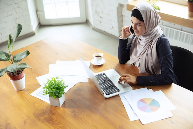 Making notes while talking on phone. arabian businesswoman wearing hijab while working at openspace or office. concept of occupation, freedom in business area, leadership, success, modern solution.