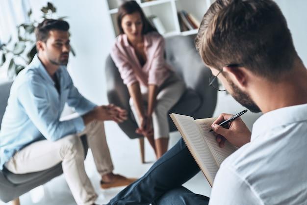 Делать заметки. молодая супружеская пара разговаривает, сидя на сеансе терапии с психологом