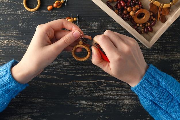 Изготовление украшений ручной работы. коробка с бисером на старый деревянный стол. вид сверху с женскими руками
