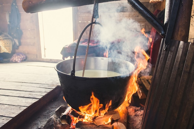 Making organic cheese in wooden mountain house. people live here in summer, milk cows, which are on pasture, boil cheese on open fire. captured on november 15, 2015 in carpathian mountains/ukraine