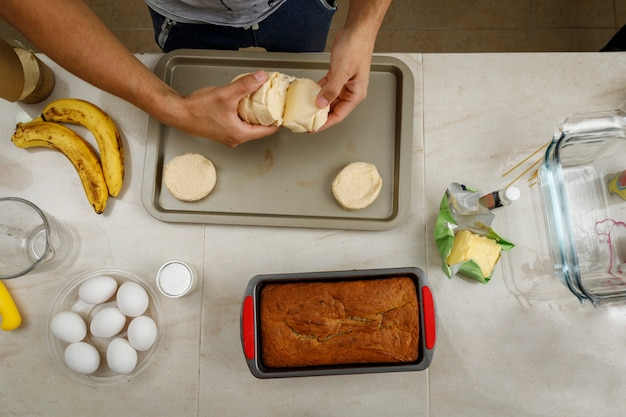 Making pastries at home hands placing biscuits on a tray to bake them on the stove