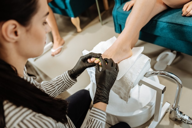 Making pedicure. dark-haired woman wearing black gloves making pedicure sitting in front of her