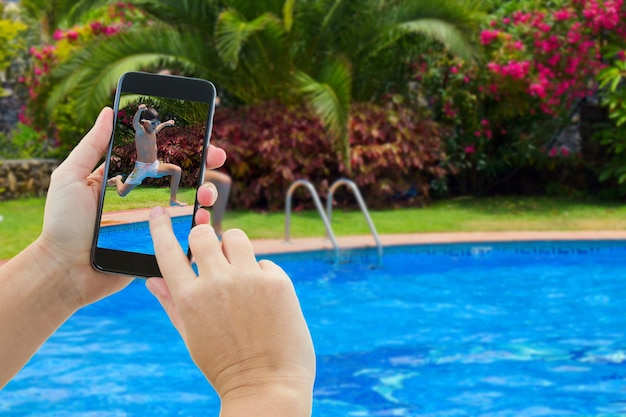 Making photo of boy jumping in cool water of swimming pool