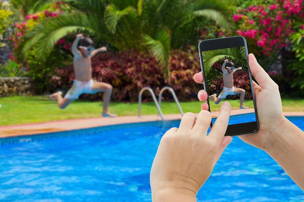 Making photo of boy jumping in water of swimming pool