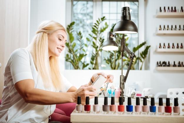 Making photo. prosperous appealing entrepreneur making photo of nail polish in her saloon