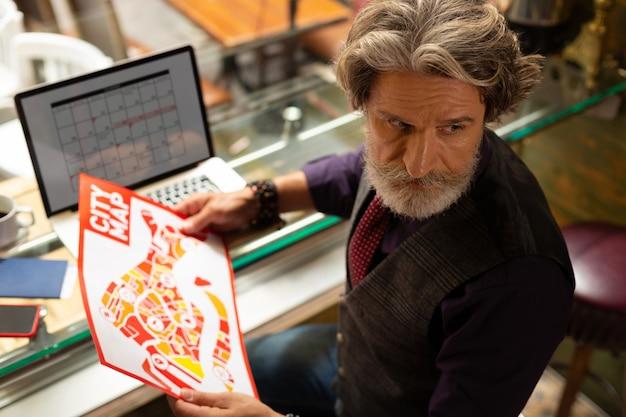 計画立案。彼の手に都市地図と彼の将来の航海を考えている彼のラップトップ上のカレンダーを持つ深刻な成人男性。