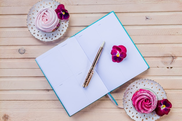 Making plans in tiny notebook for christmas.decorations and sweet pink marshmallows.colorful zephyr on wooden wall.weekly planner or to do list with pen. planning holidays concept