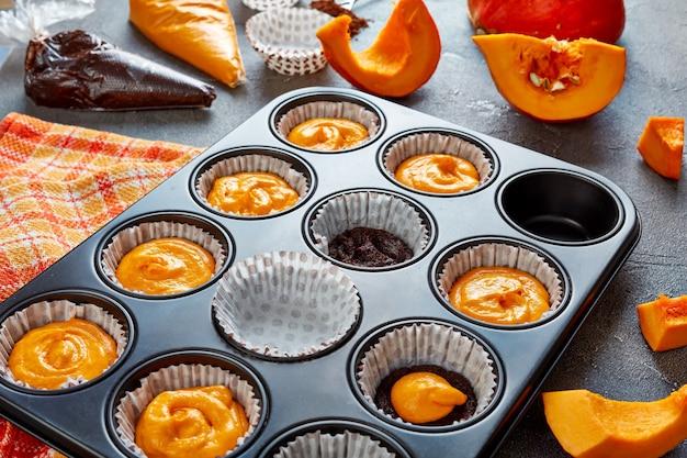 Изготовление тыквенных шоколадных маффинов на хэллоуин. ингредиенты на бетонном столе, вид сверху