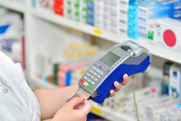 Making purchases, paying with a credit card and using a terminal on many medicines shelf in pharmacy background.