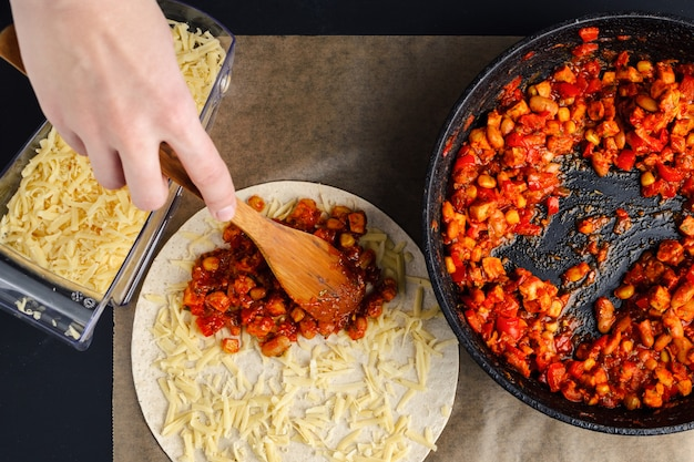 Making of quesadilla, a woman spreads a stuffing from a frying pan on a tortilla
