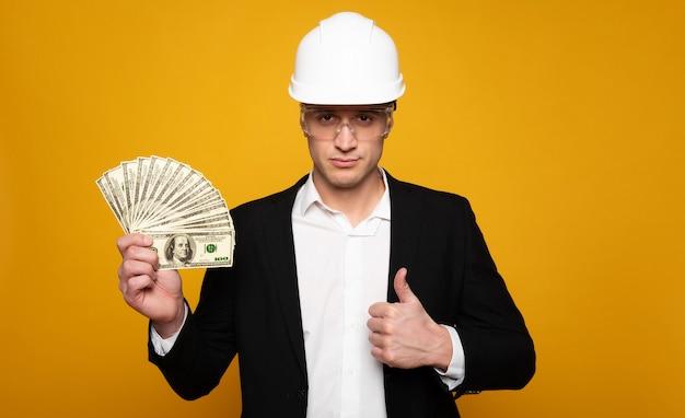 本当のお金を稼ぐ。親指を立ててカメラを見ながら右手に現金を持っている真面目なビジネスマンのクローズアップ写真。