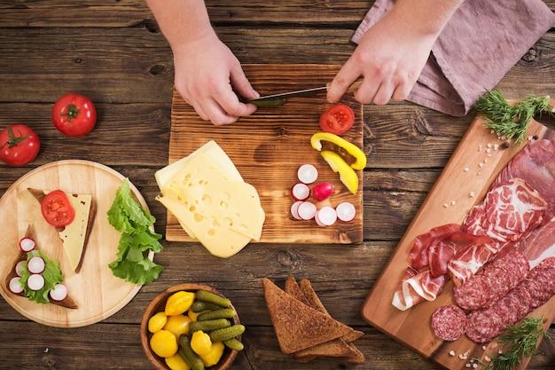 나무 테이블에 고기와 소시지로 샌드위치 만들기