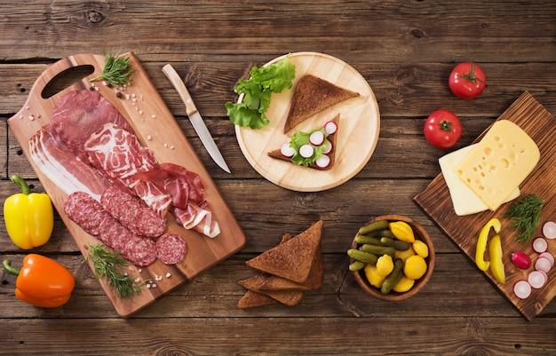 Изготовление бутербродов с мясом и колбасой на деревянный стол