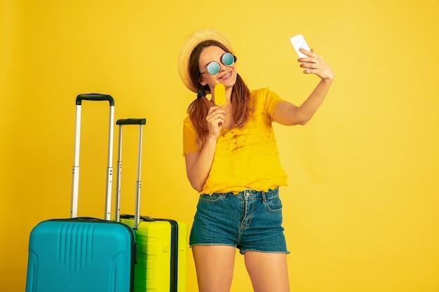 旅行前に自分撮りをする。黄色のスタジオの背景に白人女性の肖像画。キャップの美しいモデル。人間の感情、顔の表情、販売、広告の概念。夏、旅行、リゾート。