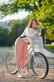 Making selfie. a dark-haired young girl with a bike making selfie in the park