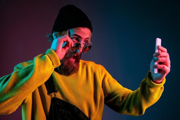 Fare selfie con gli occhiali. ritratto dell'uomo caucasico sul fondo dello studio sfumato in luce al neon. bellissimo modello maschile con stile hipster. concetto di emozioni umane, espressione facciale, vendite, annuncio.