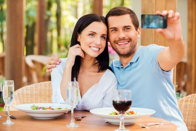레스토랑에서 셀카 만들기. 야외 레스토랑에서 함께 휴식을 취하면서 휴대전화로 셀카를 찍고 웃고 있는 아름다운 젊은 부부