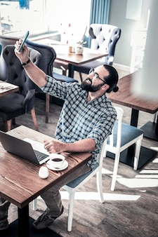 自撮り写真を作る。レストランに座って自分撮りをハイルにする現代のひげを生やした黒髪のフリーランスライター