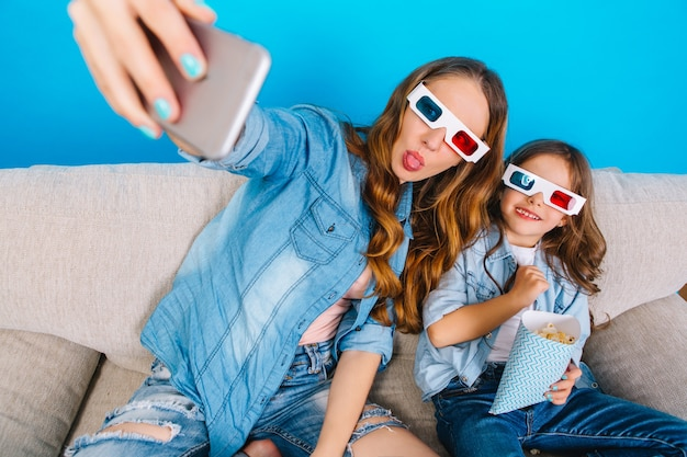 Making selfie portrait of happy moments family life. beautiful mother with long brunette hair and little daughter having fun in 3d glasses on couch isolated on blue background