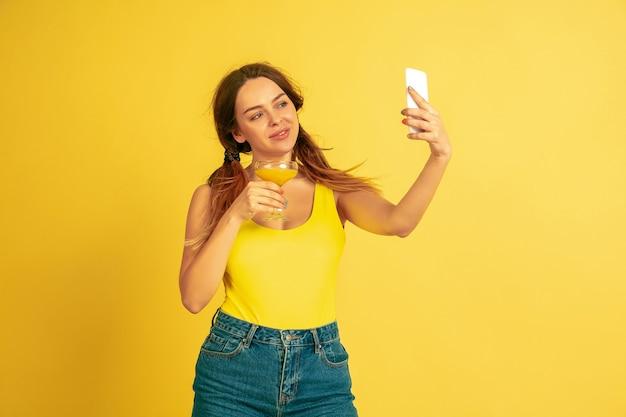 Делаю селфи, влог, улыбаюсь. портрет кавказской женщины на желтом фоне студии. красивая женская модель. понятие человеческих эмоций, выражения лица, продаж, рекламы. лето, путешествия, курорт.