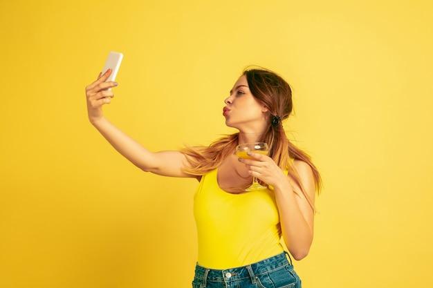 自撮り、vlog、笑顔を作る。黄色のスタジオの背景に白人女性の肖像画。美しい女性モデル。人間の感情、顔の表情、販売、広告の概念。夏、旅行、リゾート。